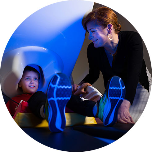 Child sits in MEG scanner with researcher assisting
