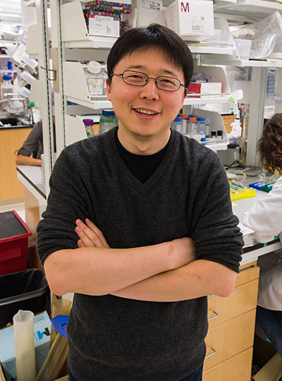 Feng Zhang with folded arms in lab