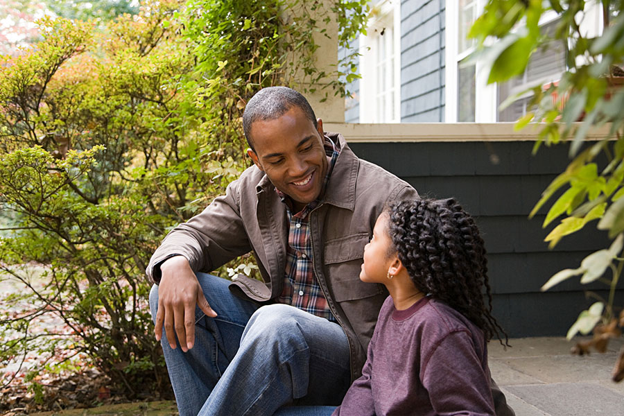 Father and young daughter sitting on a porch talking